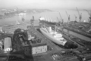 Im Trockendock von Howaldtswerke Deutsche Werft AG (HDW). In der Bildmitte Frachter INGEREN (norweg.) beim Eindocken, im Hintergrund das Fährschiff KRONPRINS HARALD (norweg.) am Oslokai.